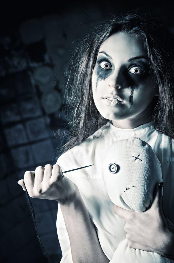 Estilo do horror disparado: menina louca assustador com boneca do moppet e agulha nas mãos imagens de stock royalty free