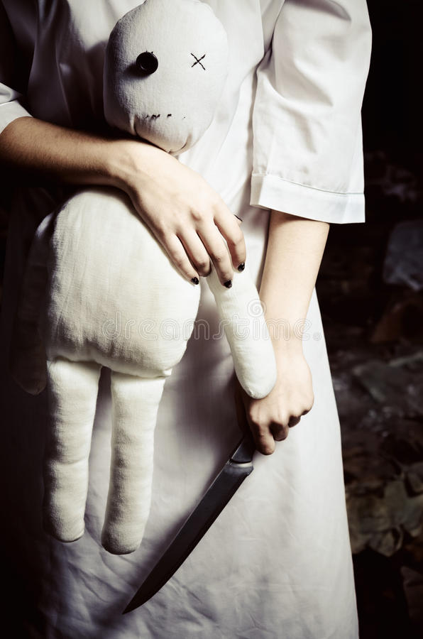 Estilo do horror disparado: boneca e faca do moppet em alguém mãos foto de stock