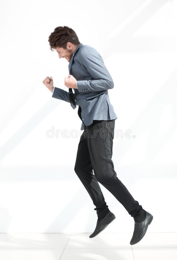 Estilo do negócio Homem novo considerável no terno completo que salta contra imagem de stock
