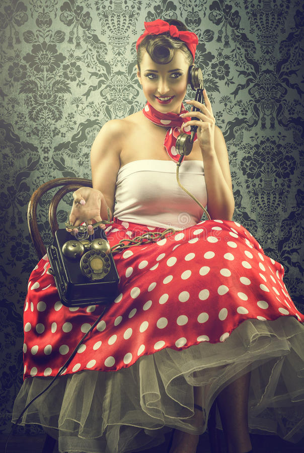 Estilo do vintage - a mulher que fala com telefone de seletor, nos às bolinhas veste-se foto de stock