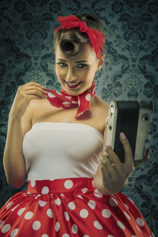 Estilo do vintage - a mulher que usa uma câmera velha nos às bolinhas veste-se fotos de stock royalty free