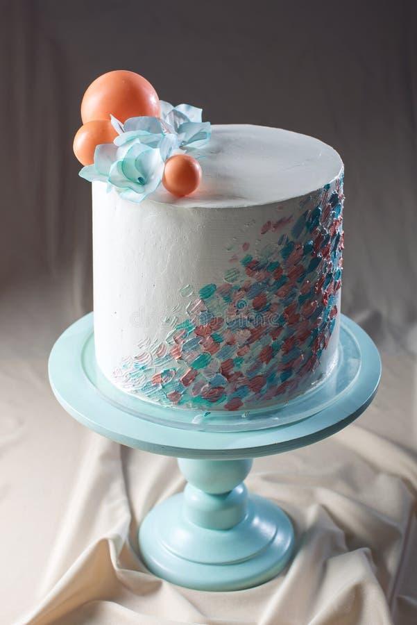 Estilo en colores pastel del pastel de bodas con las flores azules y las bolas anaranjadas fotografía de archivo