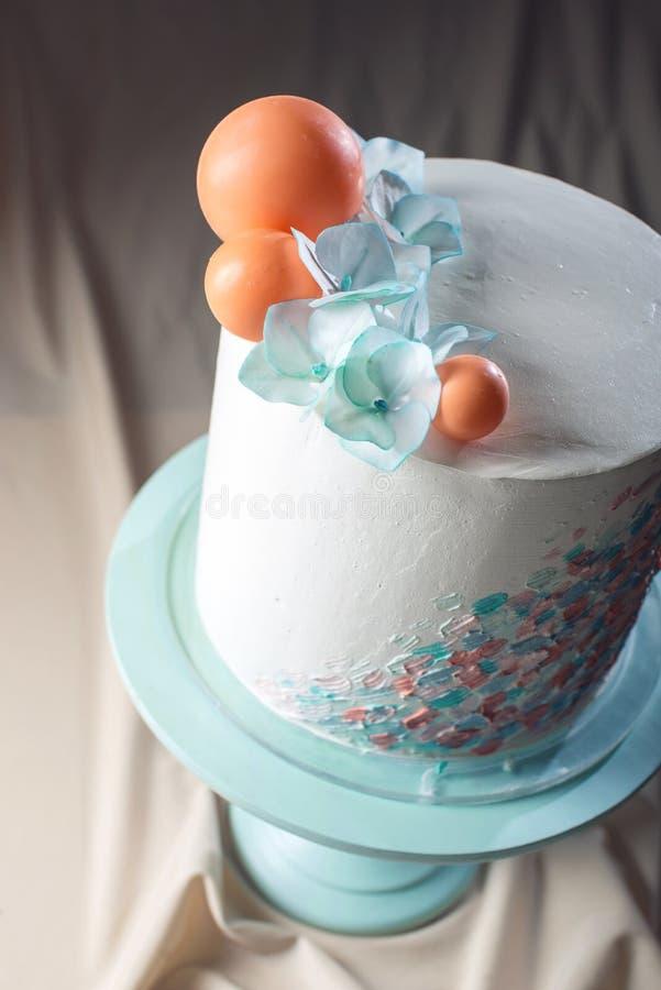 Estilo en colores pastel del pastel de bodas con las flores azules y las bolas anaranjadas imagen de archivo libre de regalías