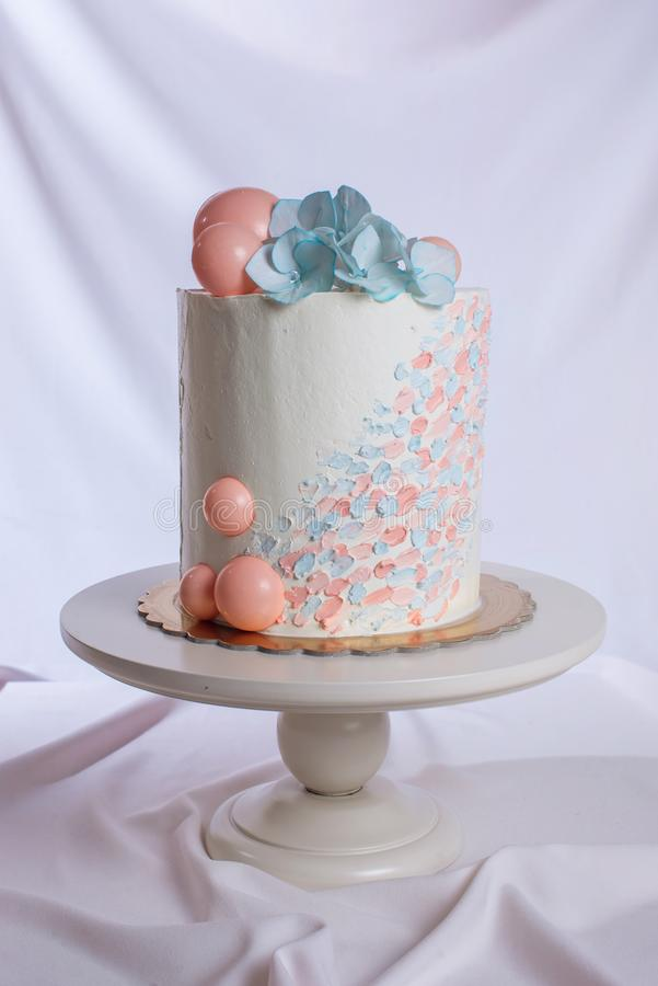 Estilo en colores pastel del pastel de bodas con las flores azules y las bolas anaranjadas foto de archivo