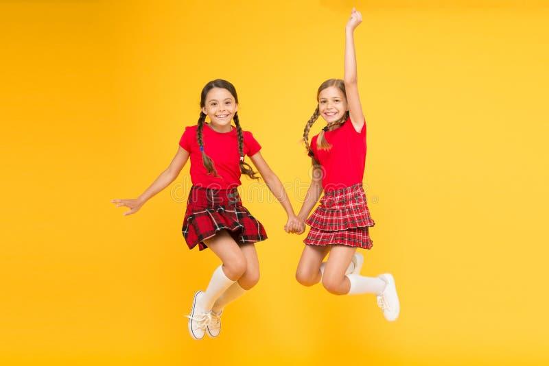 Estilo escoc?s Estudantes alegres dos amigos que saltam o fundo amarelo Comemore o feriado Feriado escocês junte imagem de stock royalty free