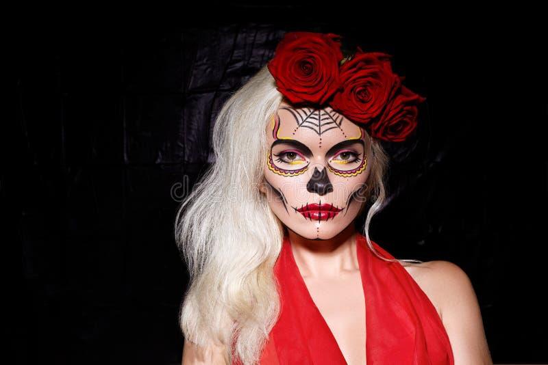 Estilo hermoso del maquillaje de Halloween Wear modelo rubio Sugar Skull Makeup con las rosas rojas Concepto de Santa Muerte foto de archivo