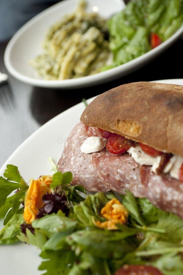 Estilo italiano Ciabatta com salame, mussarela, tomates e salada e prato da massa no fundo fotografia de stock royalty free