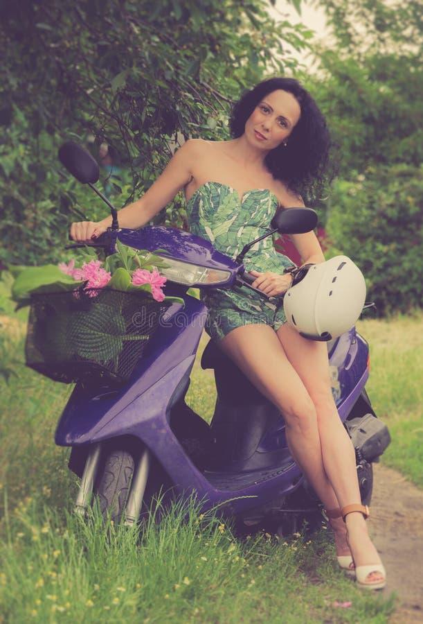 Estilo italiano Moça bonita que monta um 'trotinette' foto de stock