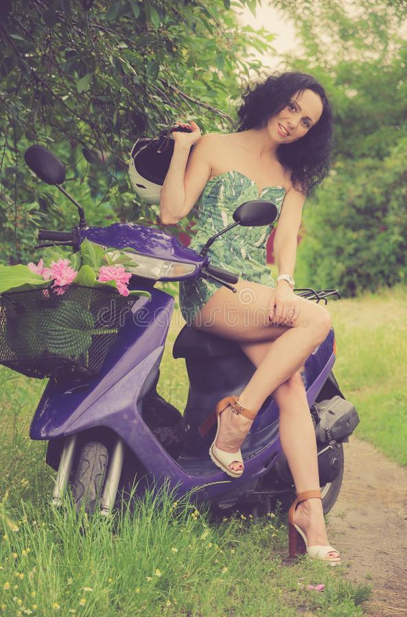 Estilo italiano Moça bonita que monta um 'trotinette' imagens de stock