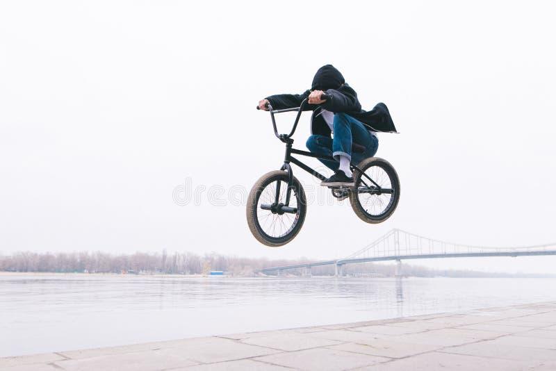 Estilo livre de BMX a criança salta em uma bicicleta de BMX O cavaleiro de BMX faz truques no fundo do rio imagens de stock
