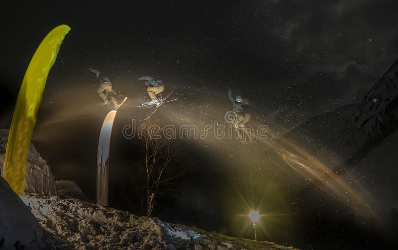 Estilo livre de salto do esquiador freerider na noite na neve exposição do borrão fotos de stock