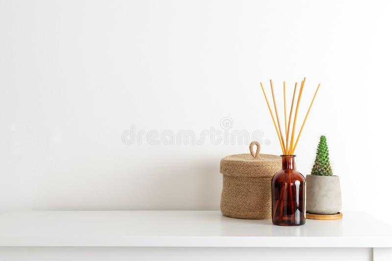 Estilo nórdico escandinavo del hygge, interior del hogar - vela, difusor del aroma del olor, pequeña cesta de la paja, estante bl fotos de archivo libres de regalías