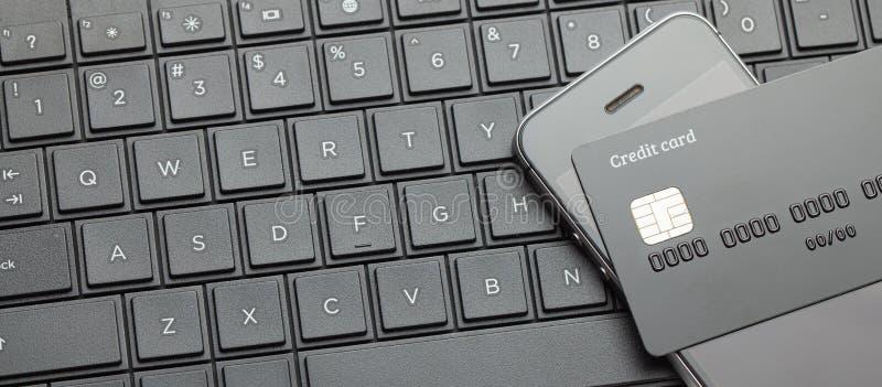 Estilo negro Tarjeta de crédito y smartphone del teléfono móvil en el teclado con el ordenador portátil Pago en línea para las co foto de archivo libre de regalías