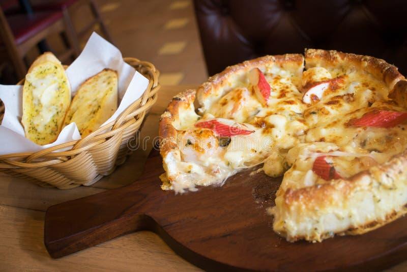 Estilo profundo de Chicago de la pizza de los mariscos del plato con pan de ajo del queso en el lado fotografía de archivo libre de regalías