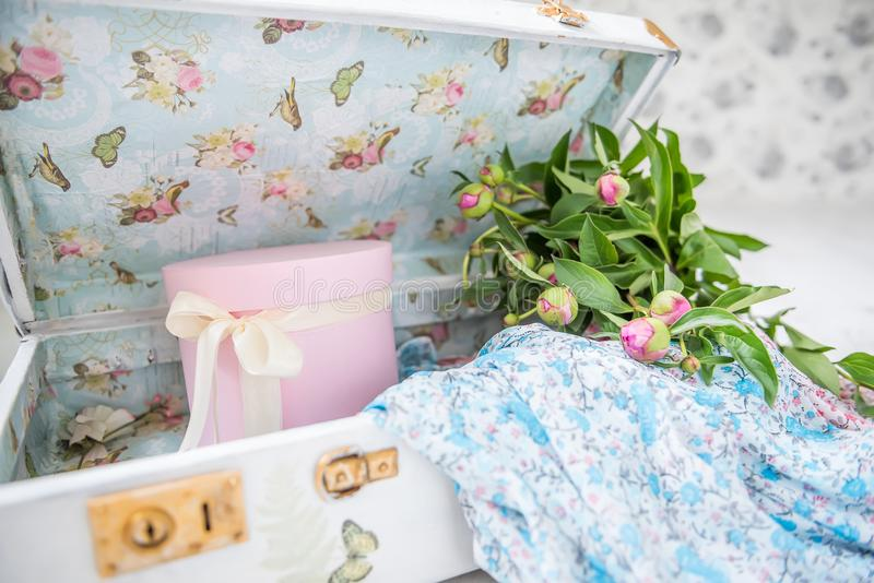 Estilo Provence da foto do vintage, mala de viagem branca, vestidos nas flores, caixas cor-de-rosa e flores das peônias imagens de stock royalty free