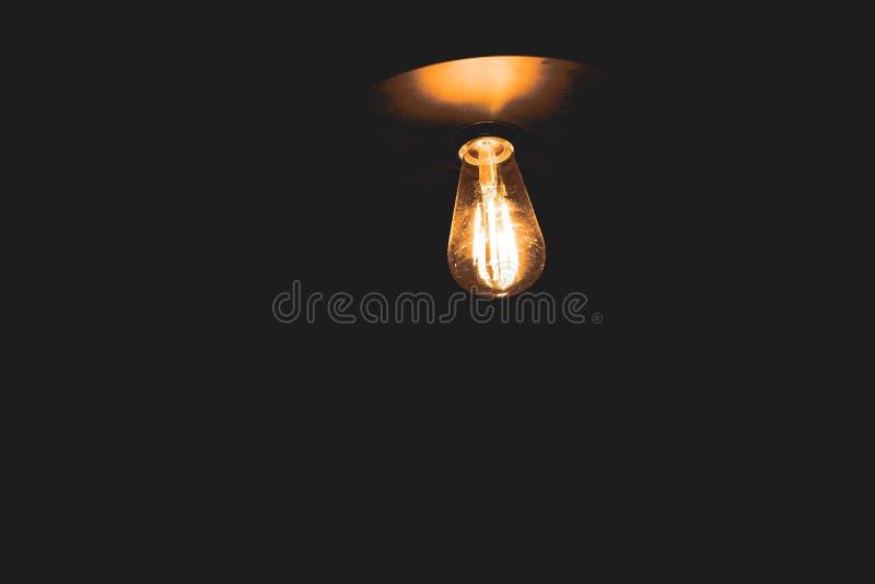 Estilo retro de la lámpara incandescente con la luz caliente que brilla intensamente en la oscuridad fotos de archivo libres de regalías