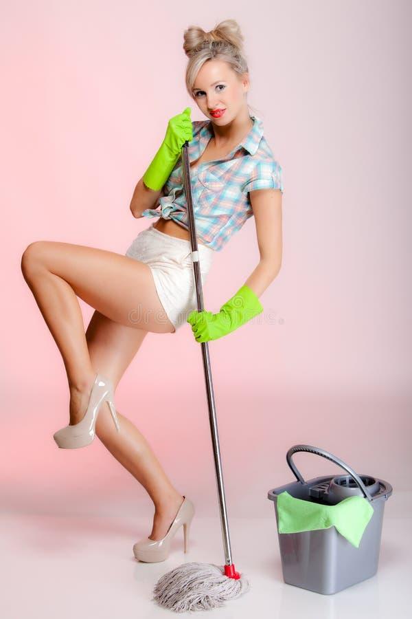 Estilo retro de la muchacha atractiva, limpiador del ama de casa de la mujer con la fregona fotografía de archivo