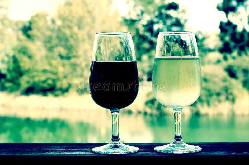 Estilo retro del filtro dos vidrios de vino, blanco y rojo, en el carril de madera imagenes de archivo