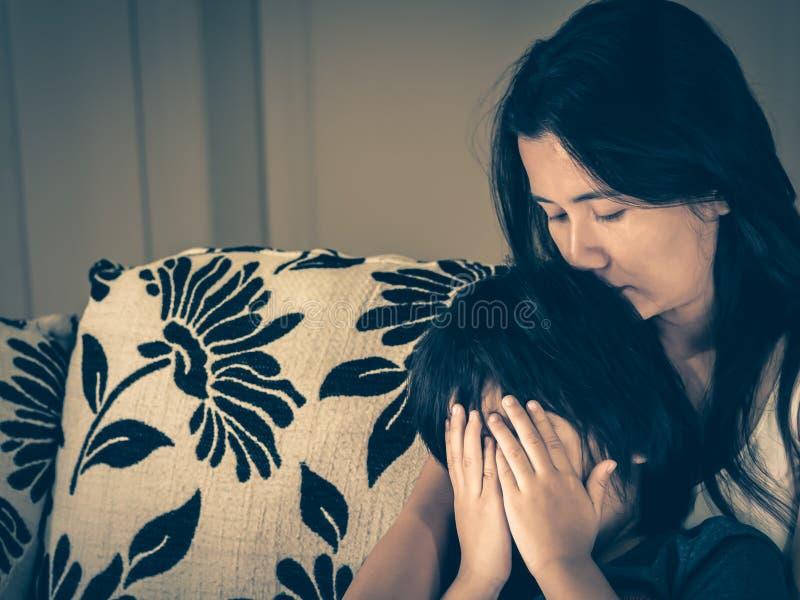 Estilo retro del niño pequeño triste que es abrazado por su madre en casa imagenes de archivo