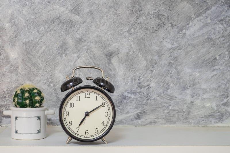Estilo retro del vintage del reloj del negro de la alarma con el pequeño cactus Pared desnuda del desván del cemento foto de archivo