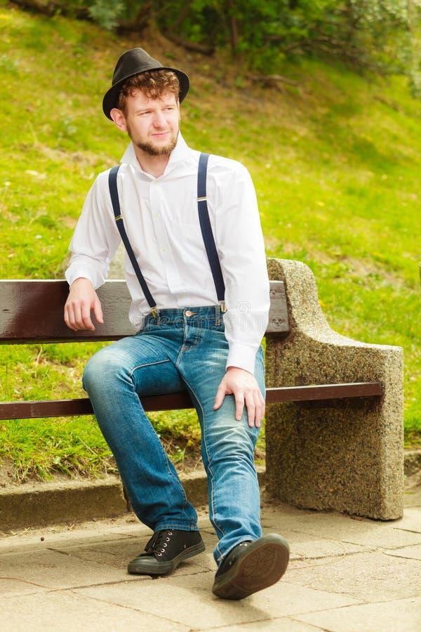 Estilo retro do homem novo que senta-se no banco no parque fotografia de stock royalty free