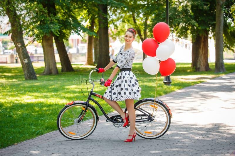 Estilo retro do pino-acima da jovem mulher bonita com bicicleta foto de stock