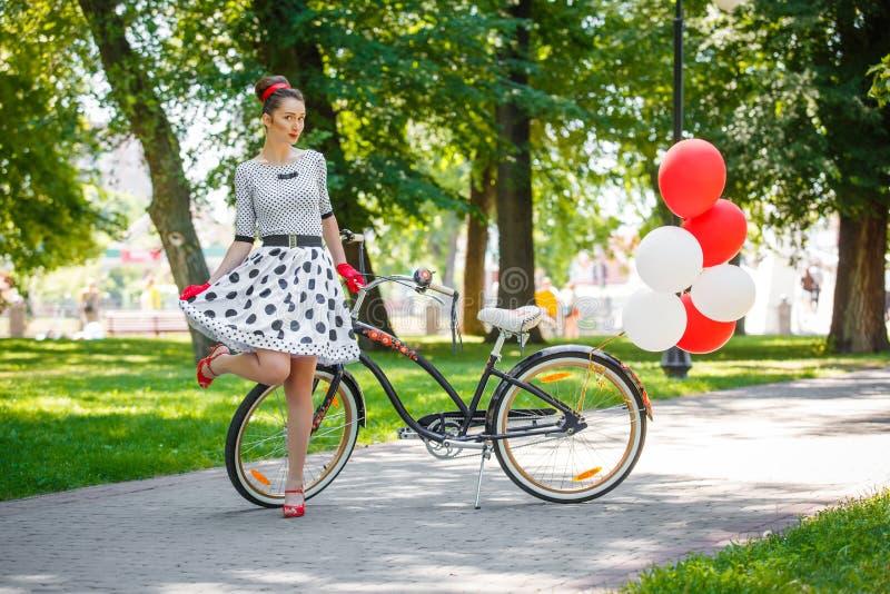 Estilo retro do pino-acima da jovem mulher bonita com bicicleta imagens de stock royalty free