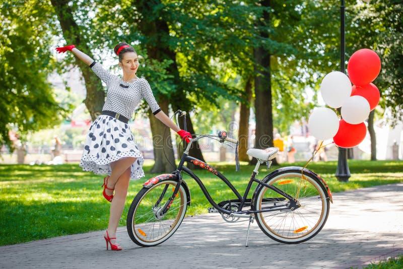 Estilo retro hermoso del perno-para arriba de la mujer joven con la bicicleta fotografía de archivo libre de regalías