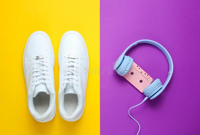 Estilo retro 80s Cultura Pop Minimalismalism Fones de ouvido com cassete ?udio, sapatilhas brancas imagem de stock