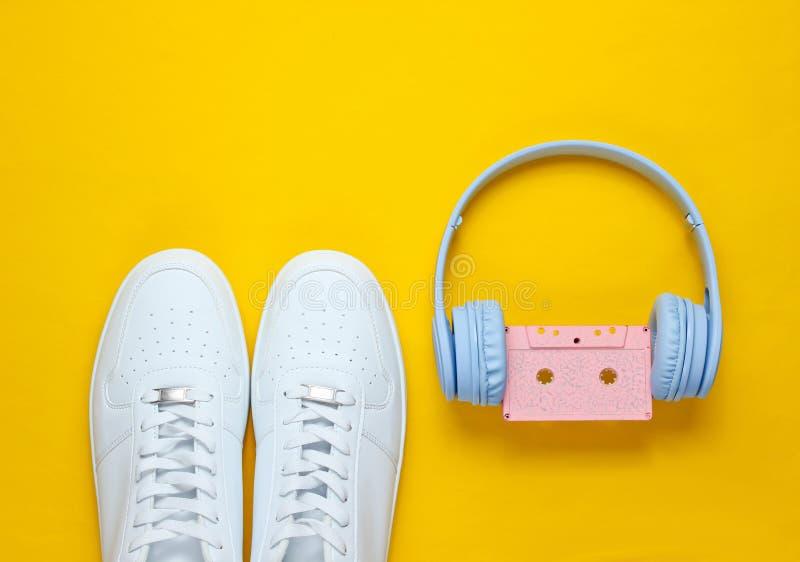 Estilo retro 80s Cultura Pop Minimalismalism Fones de ouvido com cassete ?udio, sapatilhas brancas no fundo amarelo Vista superio imagens de stock