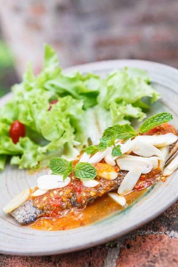 Estilo tailandés de la comida: Pescados fritos toppted con la salsa de chiles fotografía de archivo