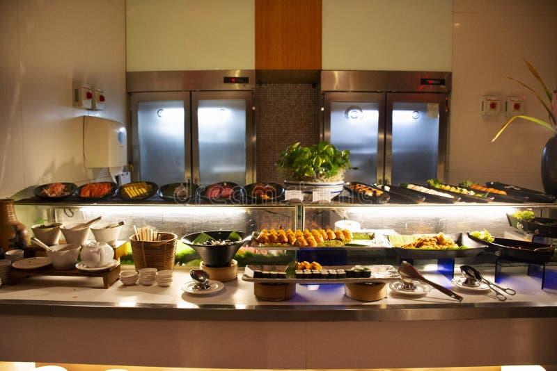Estilo tailandês alimento e da barra de sushi japoneses muito variedade que cobre na linha do alimento do bufete no restaurante e foto de stock royalty free