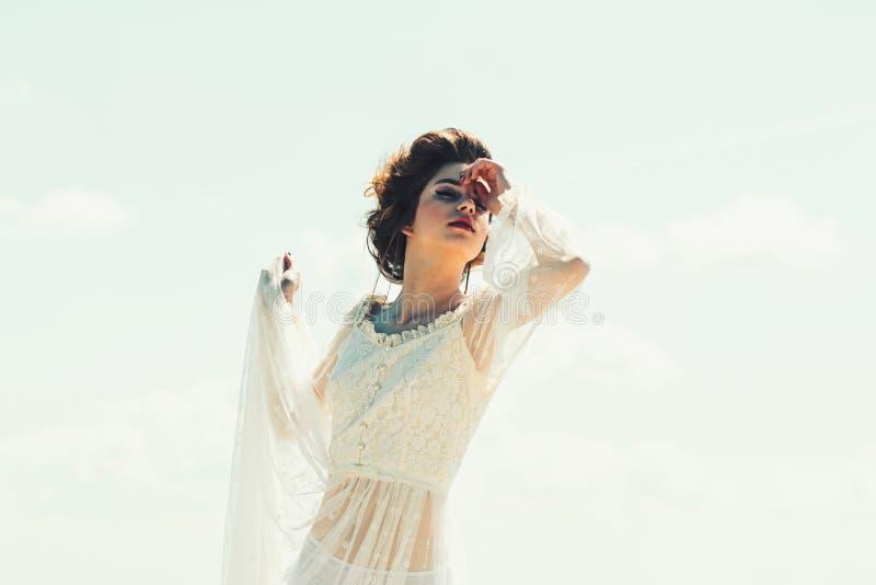Estilo y maquillaje retros para la mujer joven en el vestido blanco actitud retra de la mujer en fondo del cielo azul en estilo d imagen de archivo