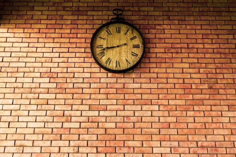 Estilos retros del vintage del reloj de pared que cuelgan en la pared de ladrillo imagen de archivo