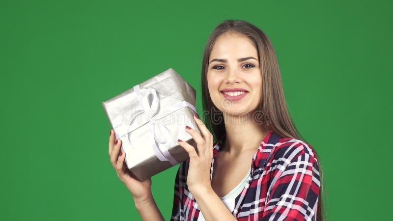 Estimation actuelle de secousse de boîte de jeune femme heureuse renversante ce qui est à l'intérieur images stock