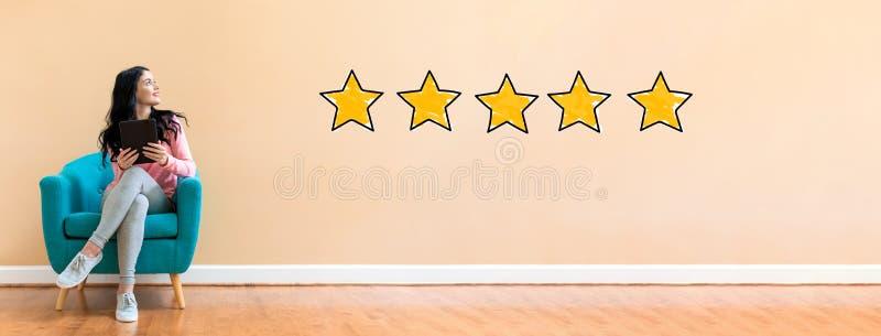 Estimation de cinq étoiles avec la femme à l'aide d'un comprimé photos stock