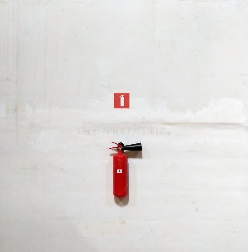 Estintore sulla parete bianca, pronto per usare fotografie stock