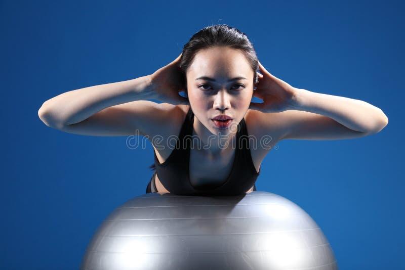 Estiramento asiático oriental da parte traseira da mulher na esfera do exercício fotografia de stock royalty free