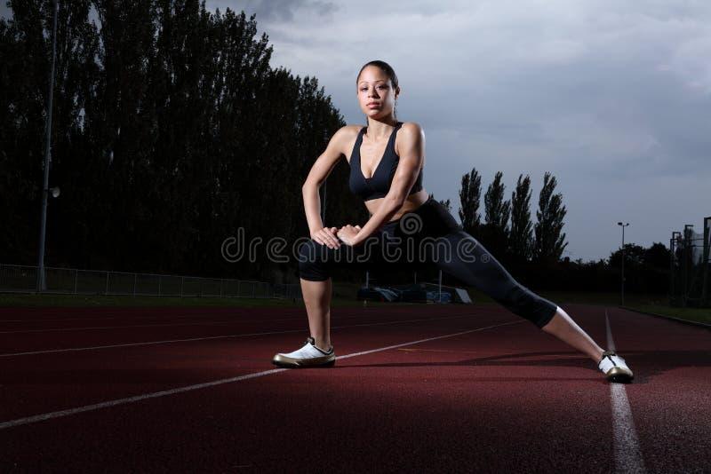 Estiramento da aptidão do atleta da mulher na trilha do atletismo foto de stock