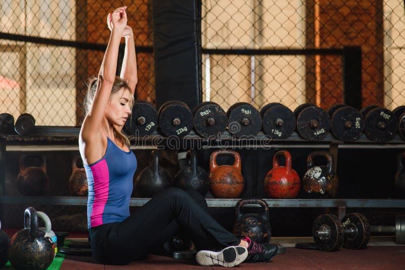 Estiramento da mulher no fundo do gym imagens de stock