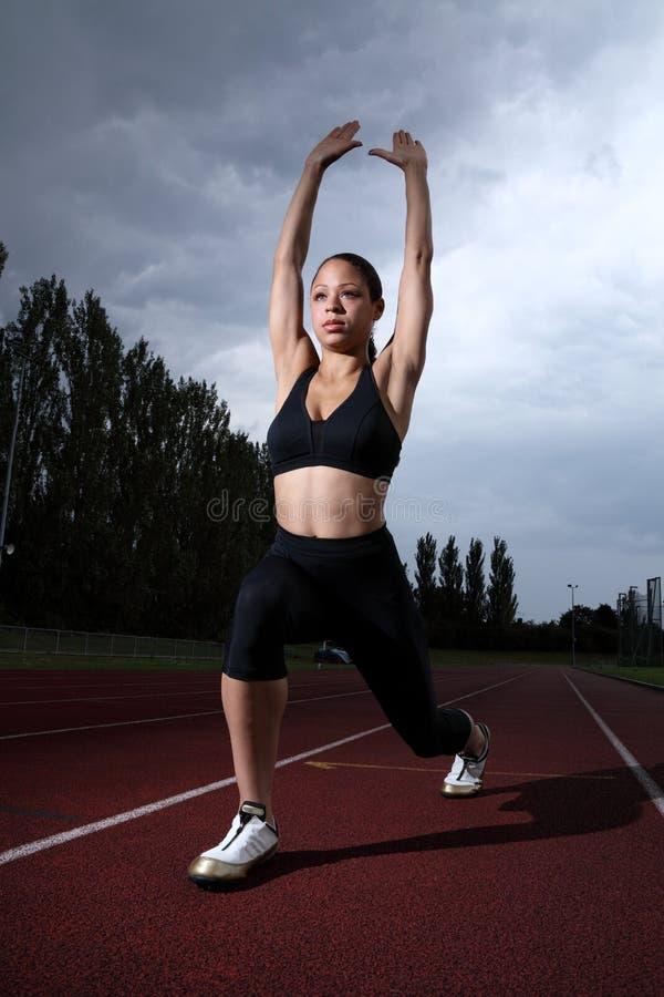 Estiramento do lunge da mulher do atleta na trilha do atletismo fotografia de stock