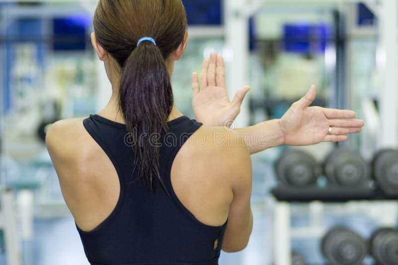 Estiramento do ombro na ginástica imagem de stock