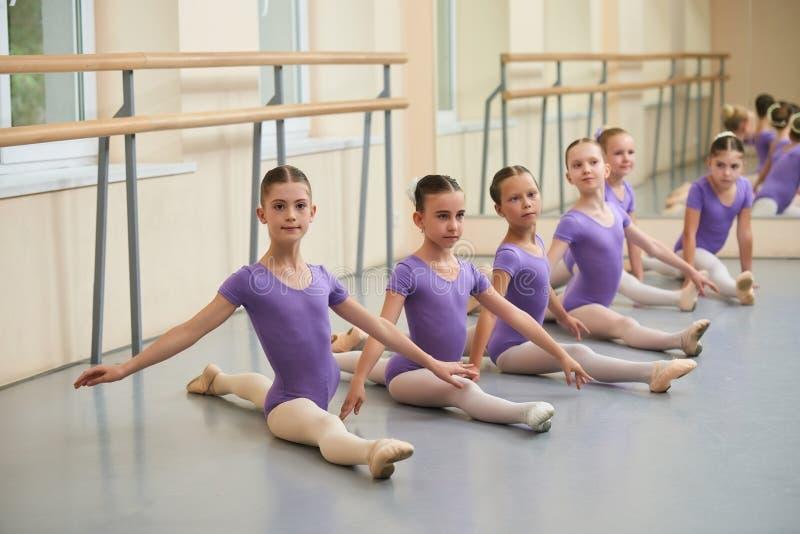 Estiramento novo das bailarinas que senta-se no assoalho imagem de stock