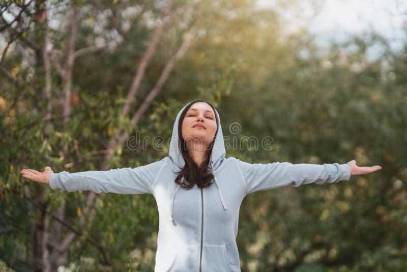 Estiramento que da posição da mulher seus braços relaxam e apreciam com fres da natureza imagem de stock royalty free