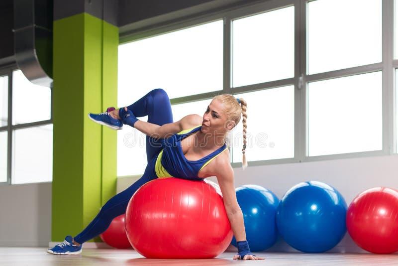 Estiramentos desportivos da mulher do ajuste na bola foto de stock royalty free