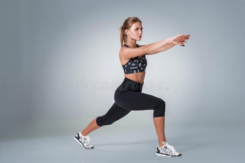 Estirando entrenamiento posture por una mujer en fondo del gris del estudio fotos de archivo