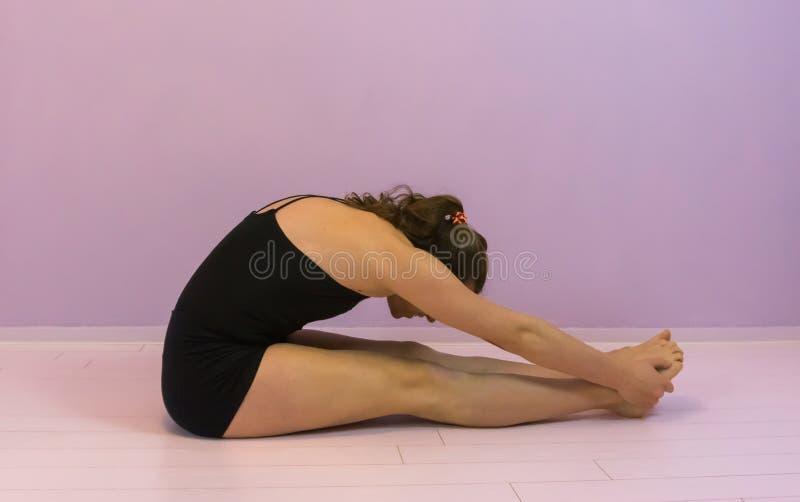 Estirando los becerros para entrenar a flexibilidad, el deporte se resuelve, elaboración joven de la muchacha del transexual de L fotos de archivo
