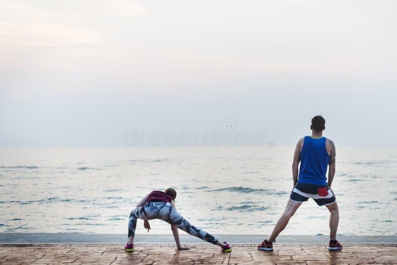 Estirar el ejercicio que entrena a concepto sano de la playa de la forma de vida imagen de archivo