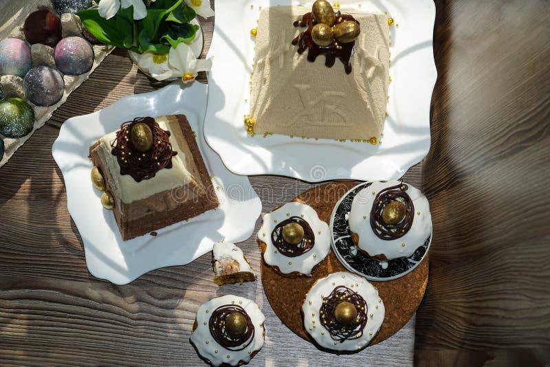 Estivelijst voor Pasen Heel wat Pasen-cakes van gestremde melkdeeg dat met chocolade en van chocoladekwartels eieren, gestremde m royalty-vrije stock foto