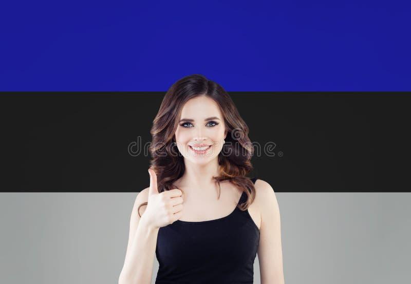 Estland Gelukkig meisje die duim tonen en op Estlandse vlagachtergrond glimlachen stock foto